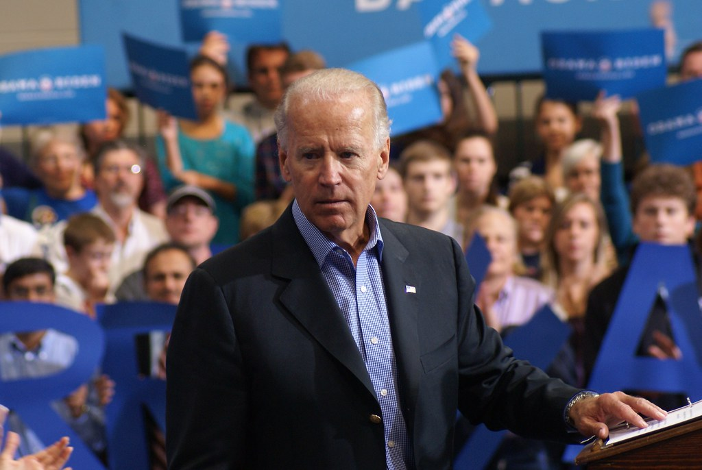 Joe Biden standing at a podium; federal funding abortions